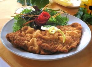 El también Schnitzel e suele acompañar de salsa de arándano rojo.