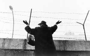 Mujer saluda sobre el muro de Berlín.